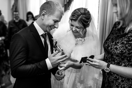 happy gorgeous bride and stylish groom exchanging wedding rings and laughing, emotional moment, official ceremony