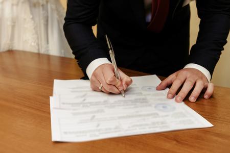 Feliz hermosa novia y elegante novio firmando documento oficial registro de bodas, momento emocional, ceremonia Foto de archivo