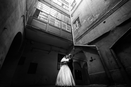 happy gorgeous bride and stylish handsome groom hugging on background of an amazing old building in light, black white Stock Photo