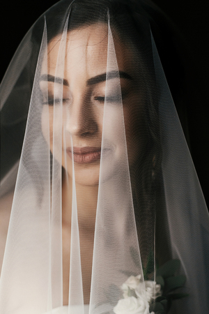 gorgeous bride with boutonniere, posing under veil near window. amazing portrait of beautiful woman getting ready for wedding in white dress, holding flowers. sensual moment
