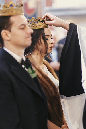priest putting on golden wedding crowns on bride and groom heads during holy matrimony in church Stock Photo