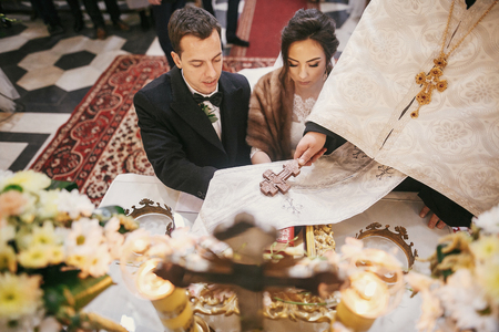 bride and groom pronouncing vows, holding hands on bible on altar and priest holding golden cross on hands during holy matrimony in church Stock Photo