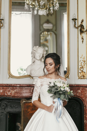 gorgeous bride in stylish dress with amazing bouquet posing in luxury room in hotel. beautiful woman holding flowers and standing near monument. sensual moment