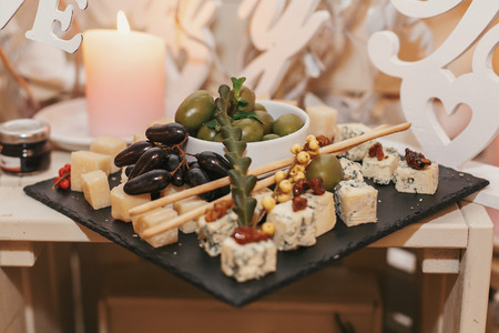 delicious cheese plate on wedding reception. table with parmesan, gorgonzola, brie and olives and grapes in restaurant. luxury catering. italian cuisine