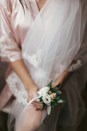 gorgeous bride holding boutonniere, sitting in robe near window. beautiful woman getting ready for wedding day, holding flowers. girl legs and veil. sensual moment. boudoir