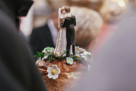 wedding cake topper. bride and groom figurines on top of wedding cake ,kissing. catering on wedding reception