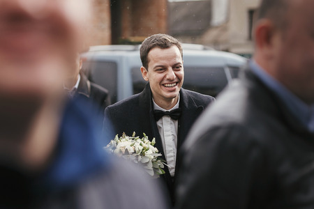 Stylish groom in suit  holding wedding bouquet and walking from car to bride among groomsmen and friends. Stock Photo