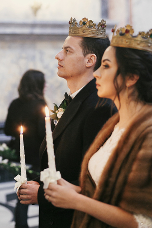 gorgeous bride and stylish groom in golden crowns, holding candles with light in  church during wedding ceremony.  spiritual newlywed couple in holy matrimony. emotional moment