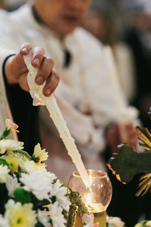 priest lightning candle and holding cross during holy matrimony in church. holy spiritual moment. candle flame