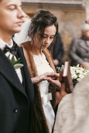 priest putting on wedding rings on bride and groom hands during holy matrimony in church. Stock Photo