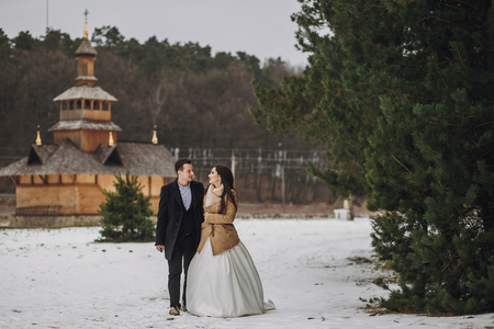 gorgeous bride and groom walking at wooden church in autumn forest. happy newlywed couple hugging in woods after holy wedding ceremony, romantic tender moment