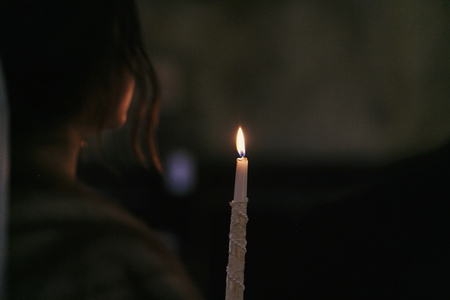 candle light in the dark in church. bride holding candle fire during holy matrimony in church. atmospheric spiritual moment. religious concept. prayer in church Stockfoto