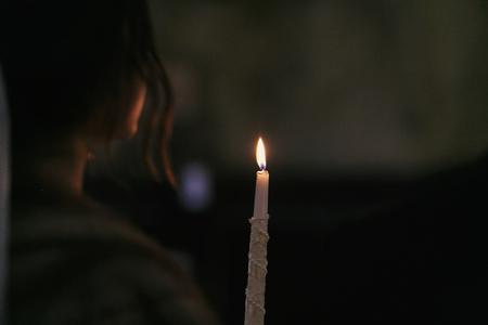 lume di candela nel buio in chiesa. sposa che tiene il fuoco di una candela durante il santo matrimonio in chiesa. momento spirituale atmosferico. concetto religioso. preghiera in chiesa