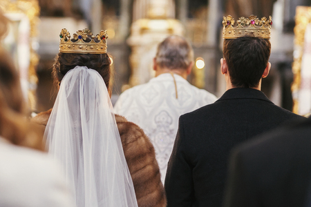gorgeous bride and stylish groom in golden crowns, standing with priest in church during wedding ceremony.  spiritual newlywed couple in holy matrimony. emotional moment