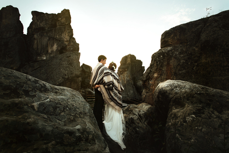 happy luxury couple newlyweds looking at sunset hugging under rustic rug in the mountains Stock Photo
