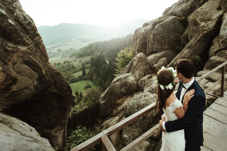 luxury happy bride and stylish groom holding each other and looking on background of sunny rocks in amazing mountains