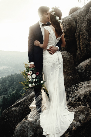 silhouettes stylish gorgeous couple newlyweds kissing  on the rocks in the mountains in the sunset