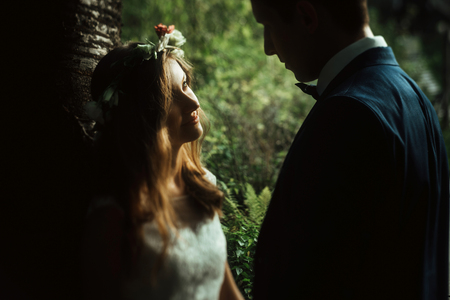 amazing sensual boho bride and stylish elegant groom looking gently with tenderness in sunny woods