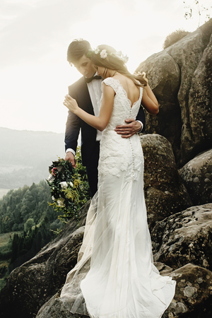 stylish gorgeous couple newlyweds standing on the rocks in the mountains in the evening light