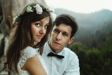 happy beautiful bride and elegant stylish groom on the top of a mountains in the evening