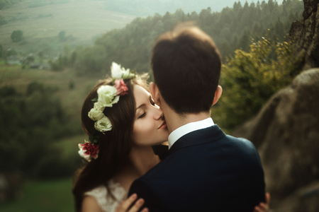 luxury happy bride and stylish groom kissing on background of  view of sunny rocks in amazing mountains Stock Photo