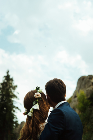 stylish boho bride and elegant groom looking at sky and hugging, happiness togetherness concept Stock Photo