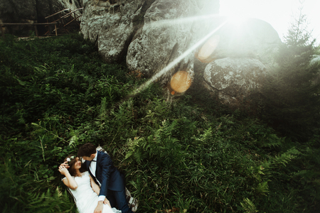 luxury happy bride and stylish groom lying on grass under sunny rocks in amazing mountains, tender moment