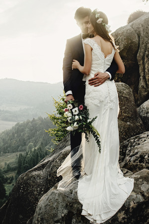 stylish gorgeous couple newlyweds kissing on the rocks in the mountains in the evening light