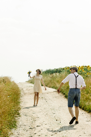 beautiful gorgeous bride and stylish handsome groom, rustic couple walking and holding hands in a sunny field Stock Photo