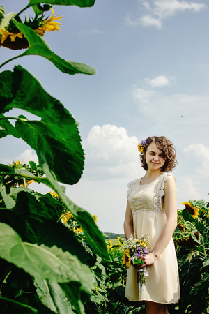 stylish gorgeous rustic bride with bouquet in sunny sunflower field Standard-Bild - 104995659