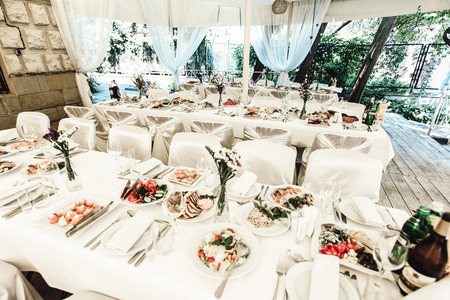 stylish luxury decorated table with flowers and delicious food, celebration wedding, catering in the restaurant