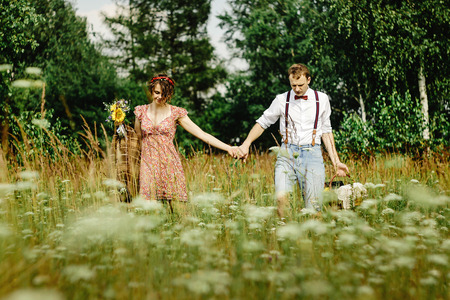 beautiful happy bride and stylish retro groom with basket holding hands, picnic time