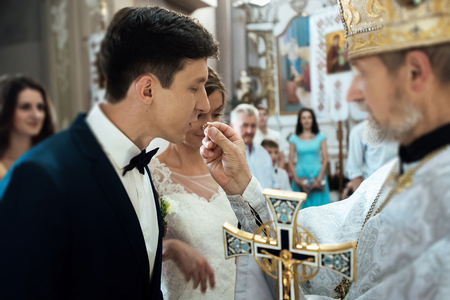 wedding ceremony of stylish elegant bride and groom in the church, exchange wedding rings