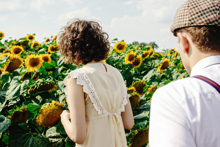 beautiful gorgeous bride and stylish handsome groom, rustic couple in a sunflower sunny field Stock Photo