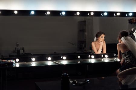 élégante mariée magnifique se maquiller dans le salon de beauté de luxe avec de grands miroirs et de la lumière