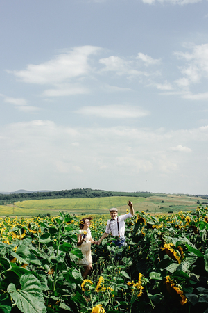 beautiful gorgeous bride and stylish handsome groom, rustic couple jumping laughing in a sunflower field Stock Photo
