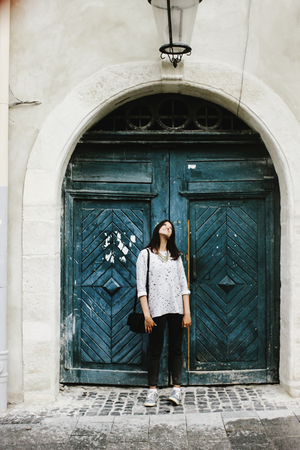 happy stylish hipster woman jumping and having fun on background of old wooden door at european street