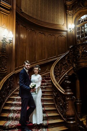 stylish luxury bride and handsome elegant groom on old wooden stairs on the background of luxury interior
