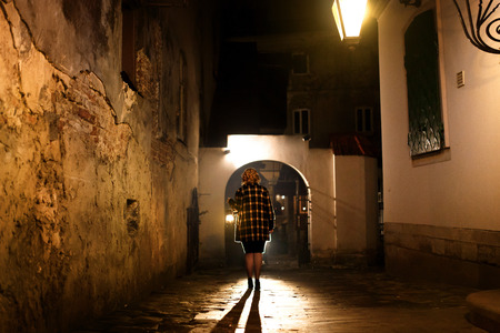 Mysterious blonde woman in elegant retro coat with old oil lantern walking in old French street in Paris, noire atmosphere, investigating crime, detective concept 写真素材