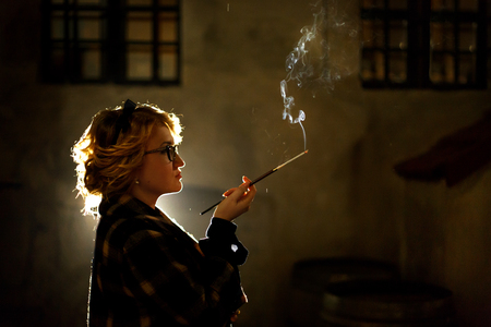 Elegant sexy woman holding cigarette and smoking outdoors, face close-up, portrait of mysterious woman in vintage coat, french noire atmosphere, detective concept Banco de Imagens