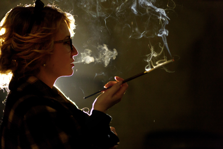 Elegant sexy woman holding cigarette and smoking outdoors, face close-up, portrait of mysterious woman in vintage coat, french noire atmosphere, detective concept Stock Photo