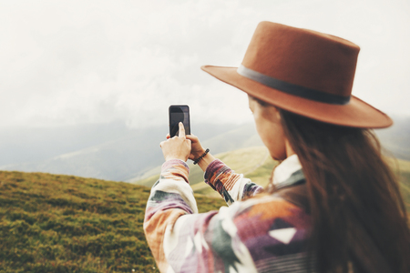 stylish traveler girl in hat with windy hair holding phone and taking picture on top of sunny mountains. travel and wanderlust concept. space for text. back view. amazing atmospheric moment Stock Photo