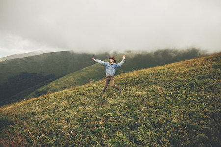 stylish traveler man in hat jumping on top of mountains with clouds. space for text. hipster guy traveling, funny emotions. amazing atmospheric moment. travel and wanderlust concept Stock Photo
