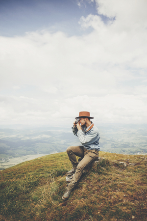 travel and wanderlust concept. stylish traveler man sitting on top of  mountains with photo camera in clouds. space for text. hipster guy traveling, taking images. amazing atmospheric moment. Stock Photo