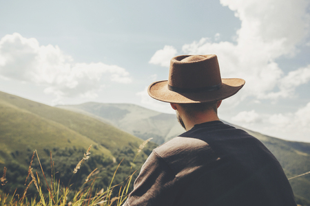 stylish traveler man in hat sitting on top of sunny mountains. travel and wanderlust concept. space for text. happy hipster traveling and camping. summer vacation
