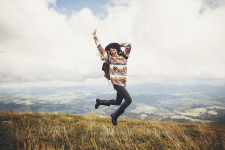stylish traveler hipster girl in hat, jumping with backpack and smiling in mountains in clouds. space for text. amazing atmospheric funny moment. travel and wanderlust concept