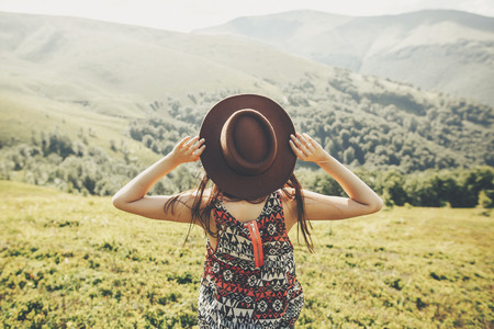 travel and wanderlust concept. traveler hipster girl holding hat, looking at sunny mountains. summer vacation. space for text. amazing atmospheric moment. happy woman traveling