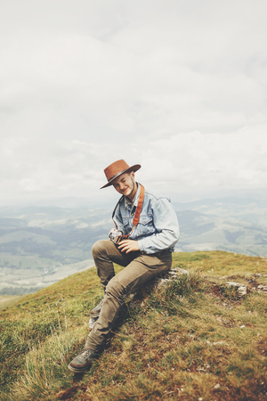 stylish traveler man sitting on top of  mountains with photo camera in clouds. space for text. hipster guy traveling, looking at hills. amazing atmospheric moment. travel and wanderlust concept