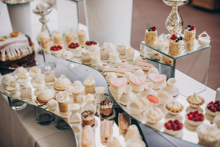 modern sweet table at celebration. stylish candy bar with delicious cakes, cookies, cupcakes with fruits in pink and white colors. luxury catering in restaurant. wedding reception Stock Photo