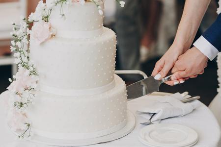 Braut und Bräutigam halten Messer und schneiden stilvolle weiße Hochzeitstorte mit Blumen. moderne große Hochzeitstorte mit rosa und weißen Rosen. Luxus-Catering im Restaurant. Hochzeitsempfang Standard-Bild